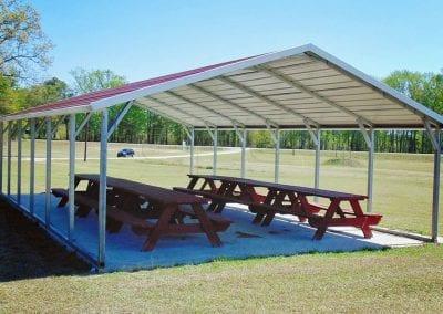 picnic tables under metal carport in park
